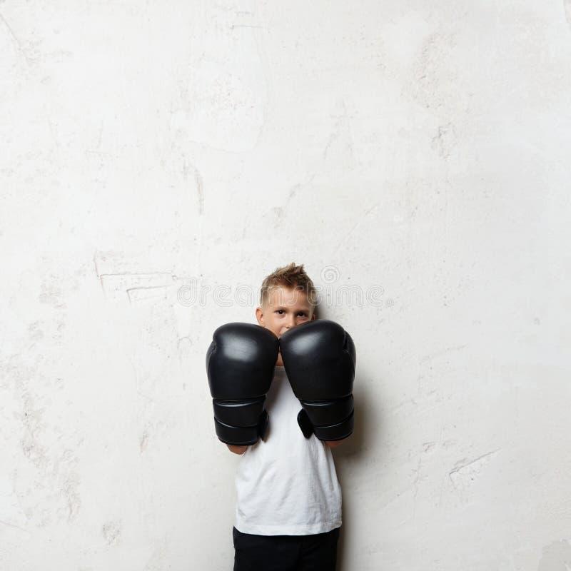 Chłopiec pozycja w bokserskich rękawiczkach i przygotowywająca zdjęcia stock