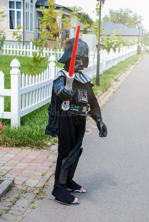 chłopiec przebierająca w Star Wars kostiumu: Darth Vader z jego kordzikiem Darth Vader fotografia stock