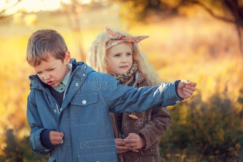 Chłopiec przedstawia gitarzysty rock and roll dla ślicznej z włosami blondynki dziewczyny w jesień parku obraz royalty free