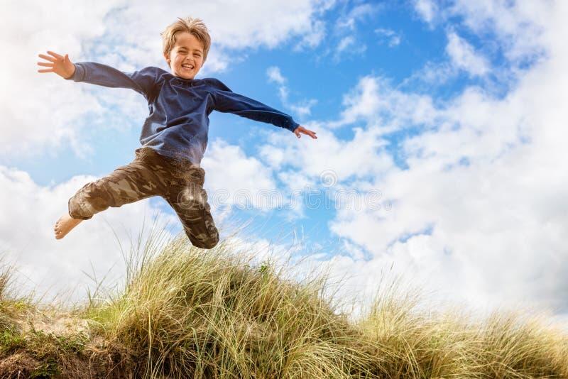 Chłopiec przeskakuje i skacze nad piasek diunami na plaża wakacje fotografia stock