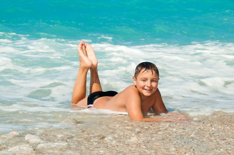 Chłopiec przy dennym lying on the beach na fala i piasku obrazy stock