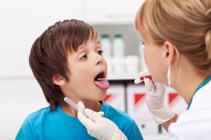 Chłopiec przy lekarką jest egzamininujący i daje biologicznym próbkom zdjęcie royalty free