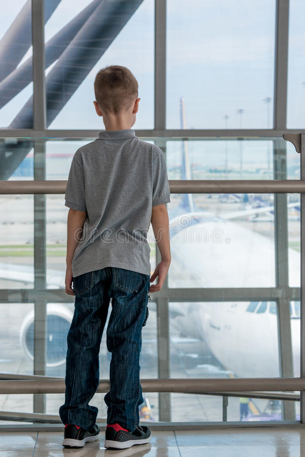 Chłopiec przy lotniskiem podziwia samolot obrazy stock