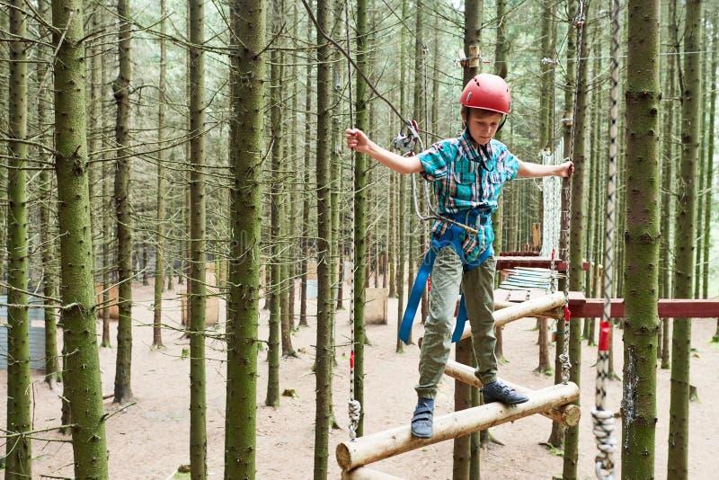 Chłopiec przy wspinaczkową aktywnością w wysokiego drutu lasu parku zdjęcie royalty free