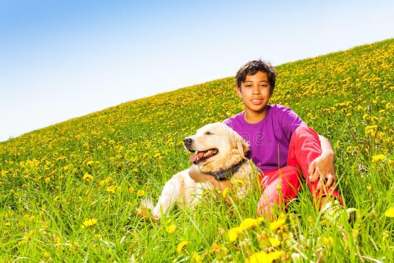 Chłopiec przytulenia psa obsiadanie na zielonej trawie w lecie obrazy royalty free