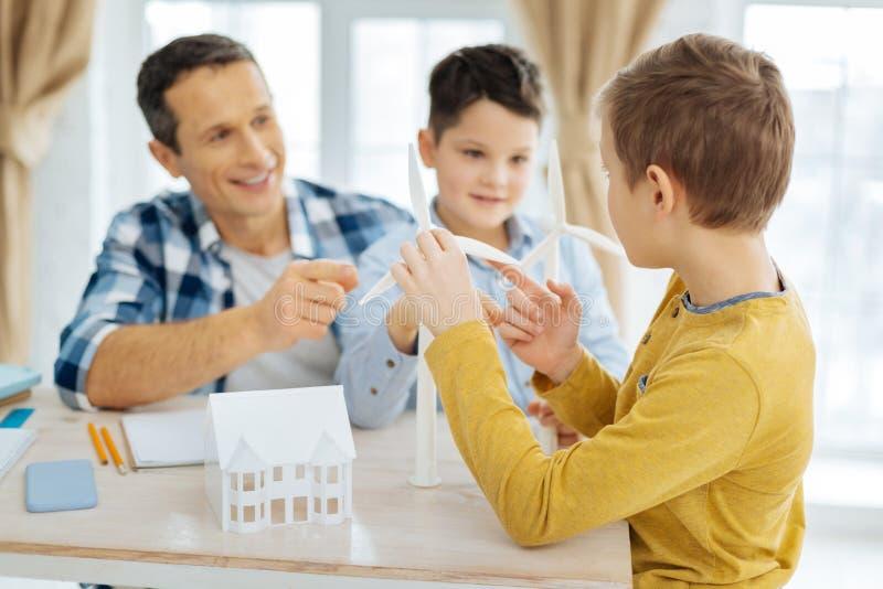 Chłopiec pyta jego ojcować o budowie silniki wiatrowi zdjęcia royalty free