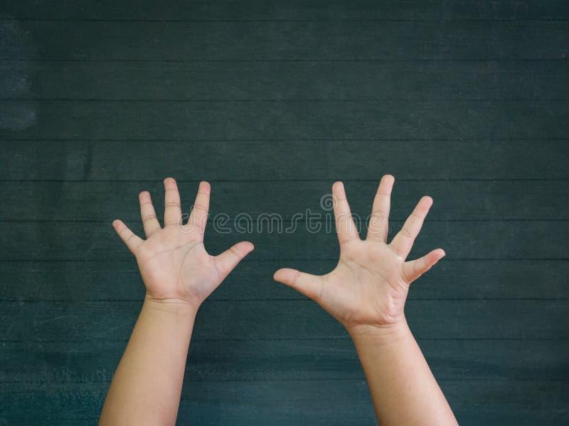 Chłopiec ręki podnoszą up na blackboard tle Szczęśliwy, Tylny obrazy stock