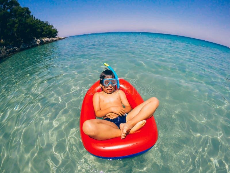 Chłopiec relaksuje na pływanie tubce fotografia stock