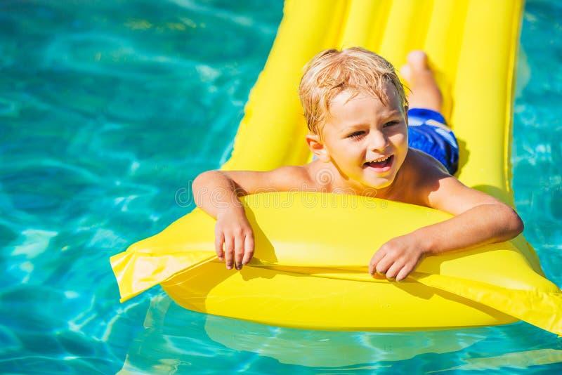 Chłopiec Relaksuje zabawę i Ma w Pływackim basenie na Żółtej tratwie zdjęcie royalty free