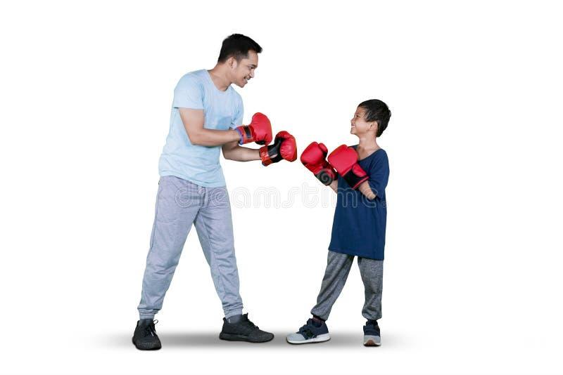 Chłopiec robi bokserskiemu ćwiczeniu z jego ojcem zdjęcie royalty free