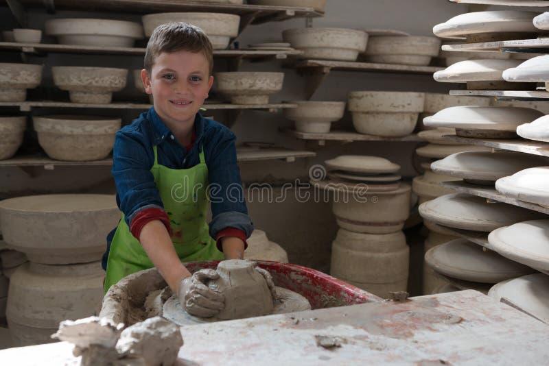 Chłopiec robi garnkowi w ceramicznym warsztacie zdjęcia royalty free