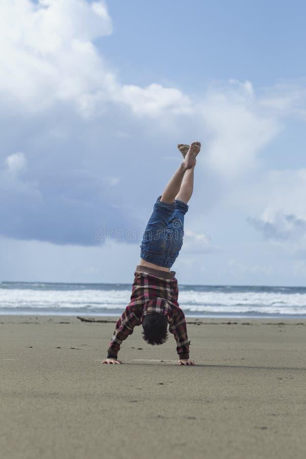 Chłopiec robi handstand na plaży zdjęcie stock
