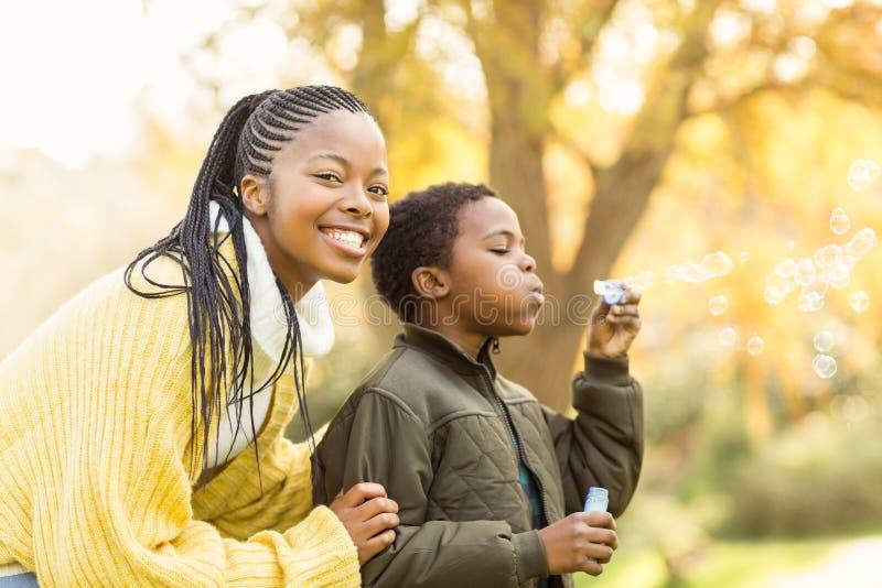 Chłopiec robi niektóre bąblom z jego matka fotografia royalty free