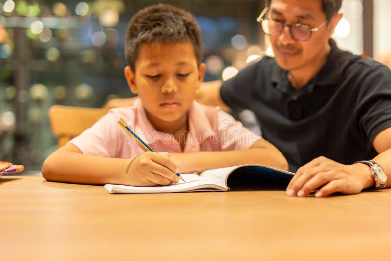 Chłopiec robi pracie domowej z ojcem w domu obrazy stock