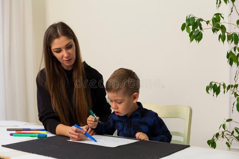 Chłopiec rysuje markierów od lekcji matki fotografia royalty free