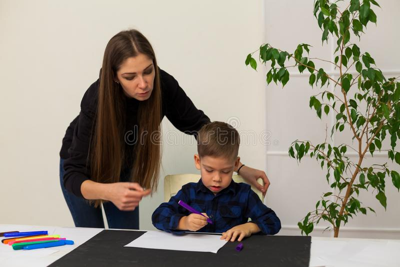 Chłopiec rysuje markierów od lekcji matki obraz stock