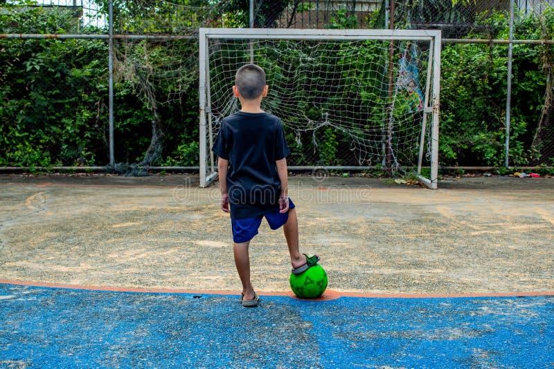 Chłopiec są wokoło strzelać futbol Na smole obraz stock