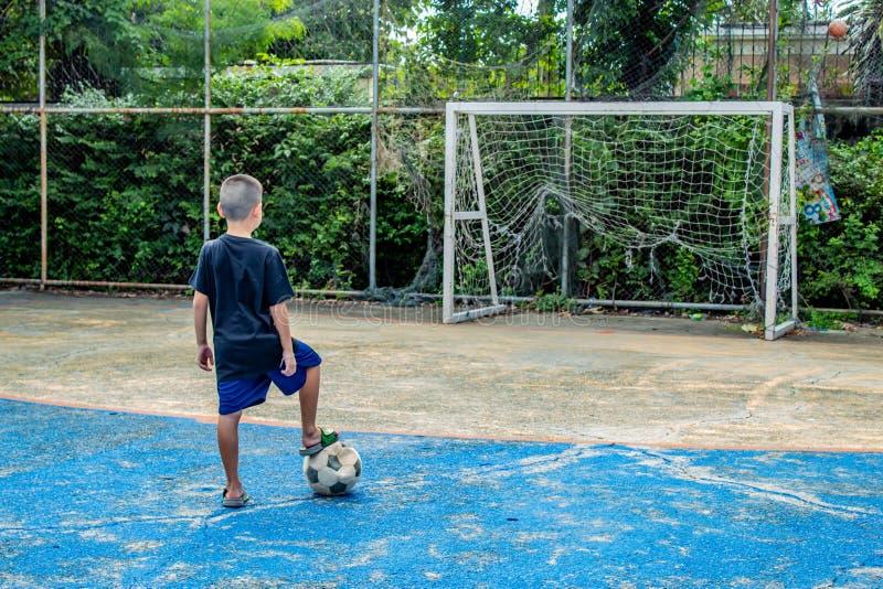 Chłopiec są wokoło strzelać futbol Na smole zdjęcie royalty free