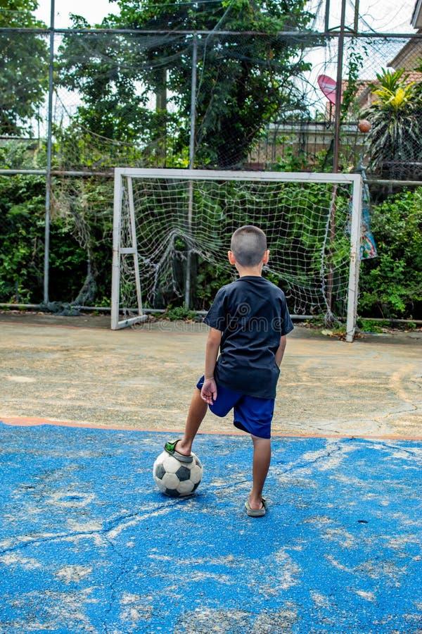 Chłopiec są wokoło strzelać futbol Na smole zdjęcie stock