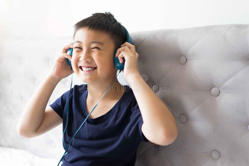 Chłopiec słucha muzyka na łóżku przy sypialnią dla relaksuje obrazy stock