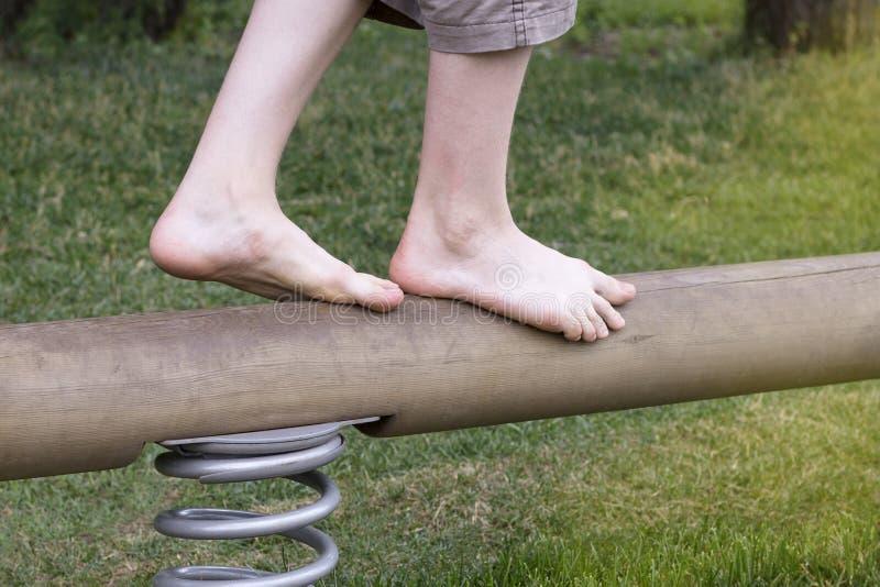 Chłopiec ` s nogi iść na niekończący się balansowym promieniu obrazy royalty free