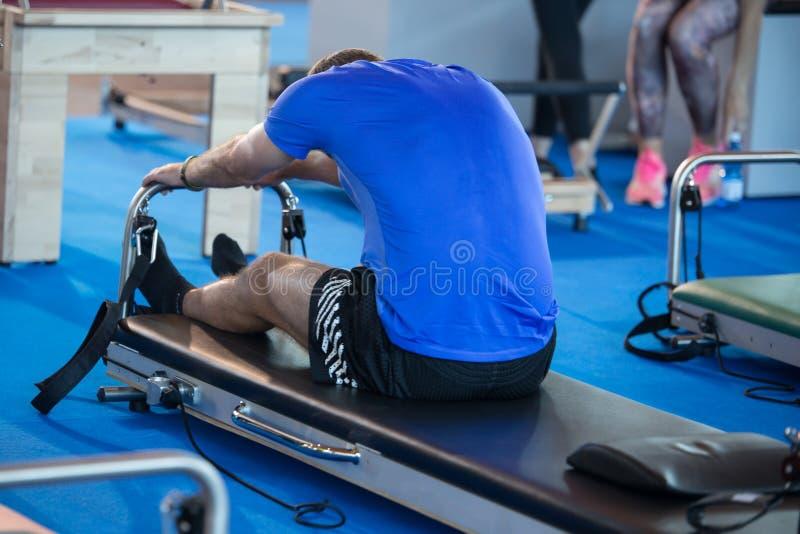 Chłopiec siedzący z nogami wypchanym, robiąc 'Stretching Before Fitness Activity in Gym' zdjęcie stock