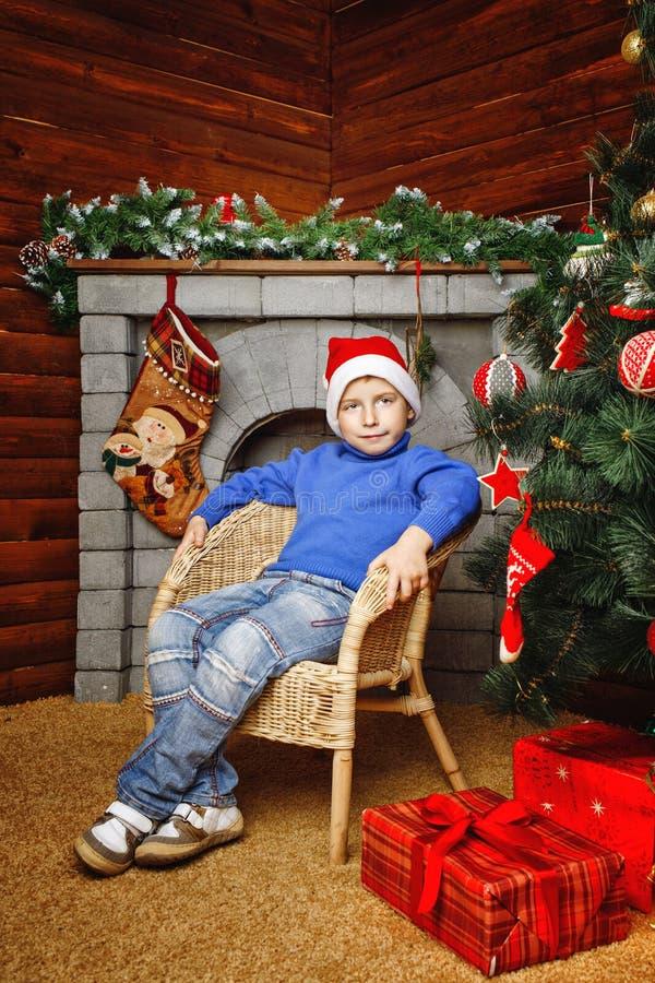 Chłopiec siedzi blisko choinki i prezentów zdjęcie royalty free