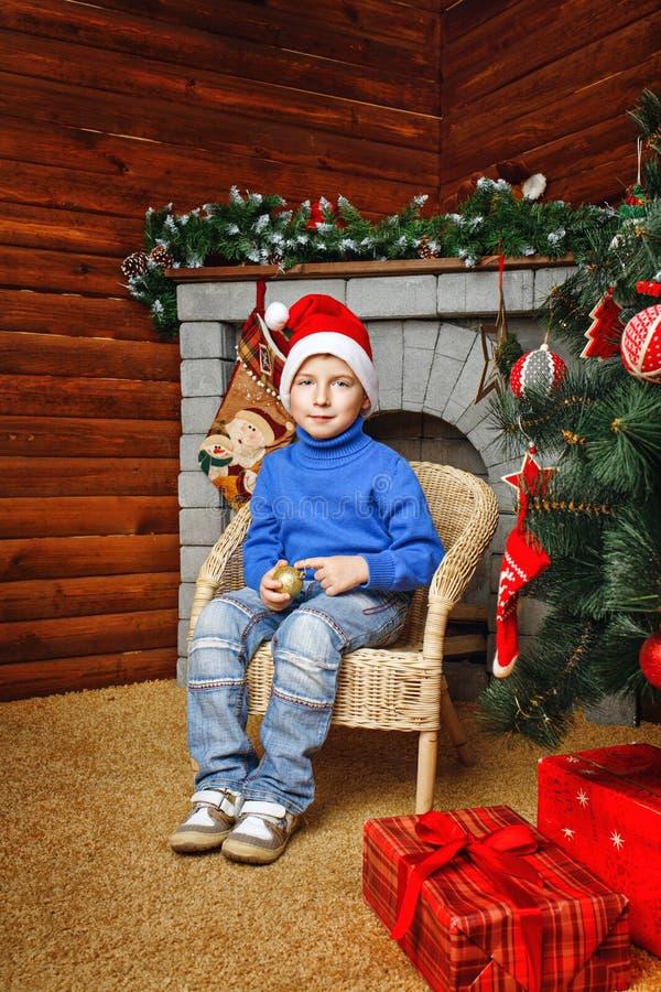 Chłopiec siedzi blisko choinki i prezentów obrazy stock