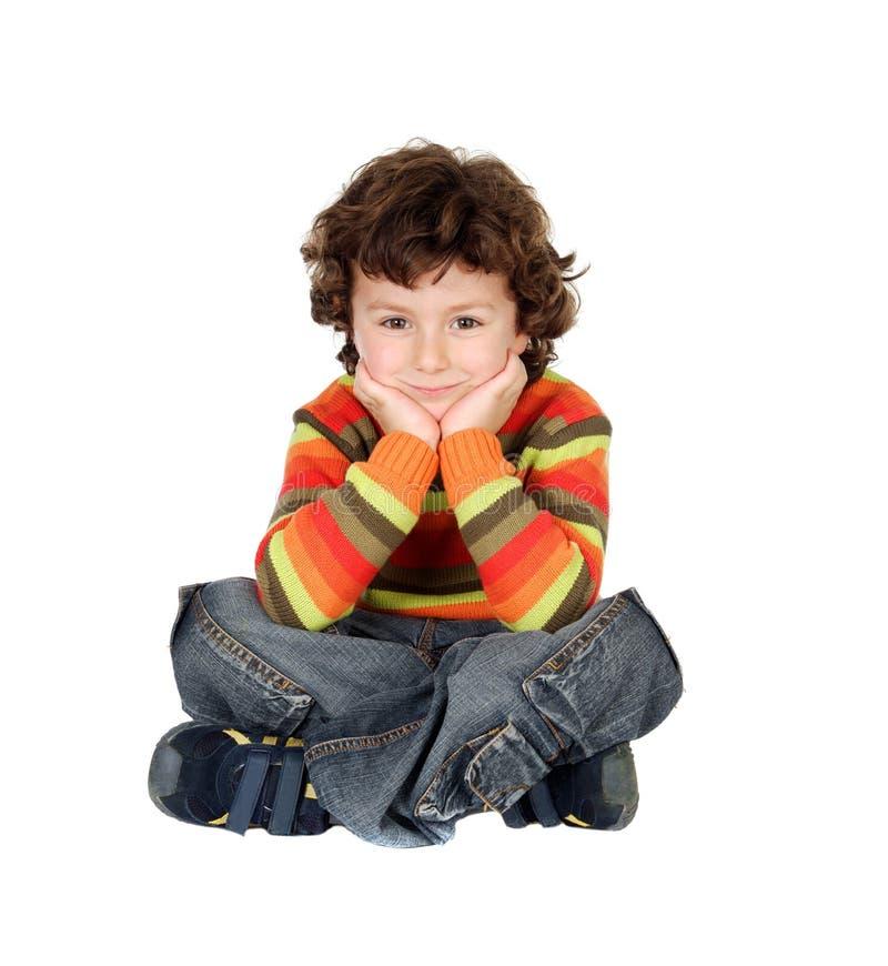 Chłopiec siedzi na białym podłogowym główkowaniu z siedem lat fotografia stock