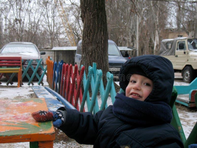 Chłopiec siedzi na boisku podczas zima spaceru obrazy royalty free