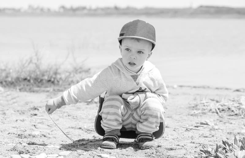 Chłopiec siedzi na brzeg jezioro obrazy stock