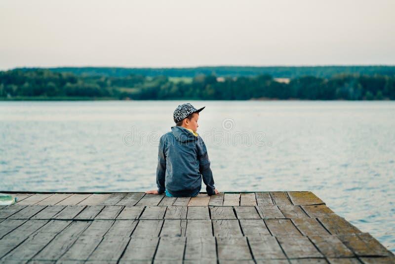 Chłopiec siedzi na moście blisko jeziora fotografia stock