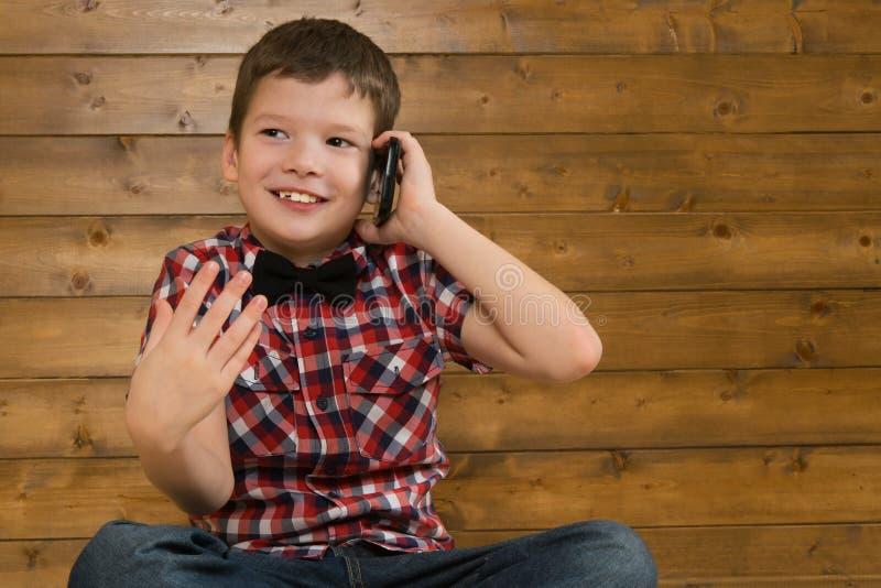 Chłopiec siedzi na podłoga, opowiada na telefonie, przeciw tłu drewniana ściana zdjęcie stock