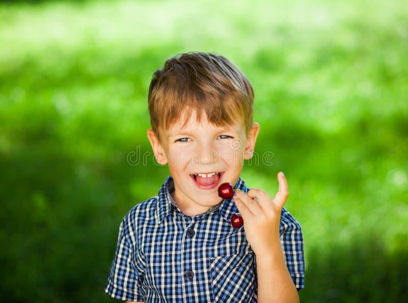 Chłopiec siedzi na zielonej trawie i je truskawki w lato ogródzie, ostrość na jagodach zdjęcia royalty free
