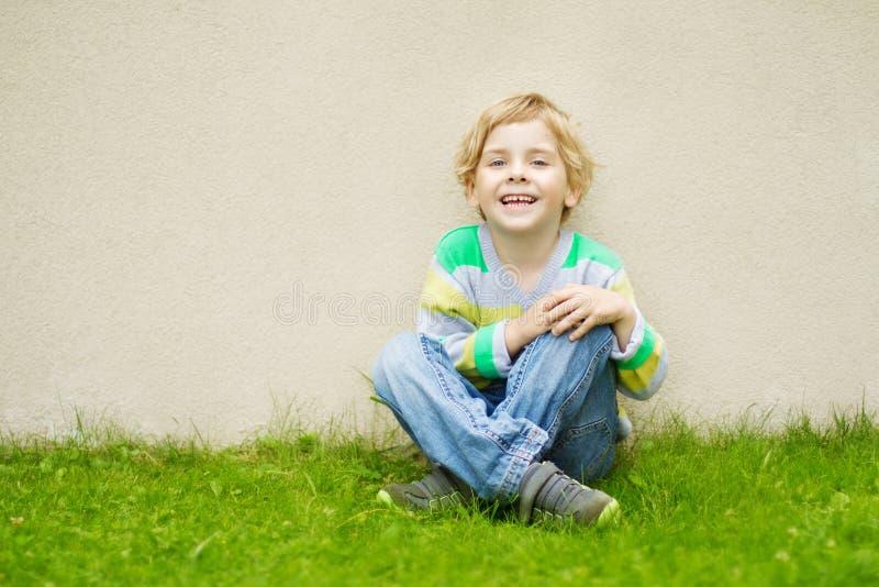 Chłopiec siedzieć plenerowy na zielonej trawie nad betonową ścianą zdjęcia stock