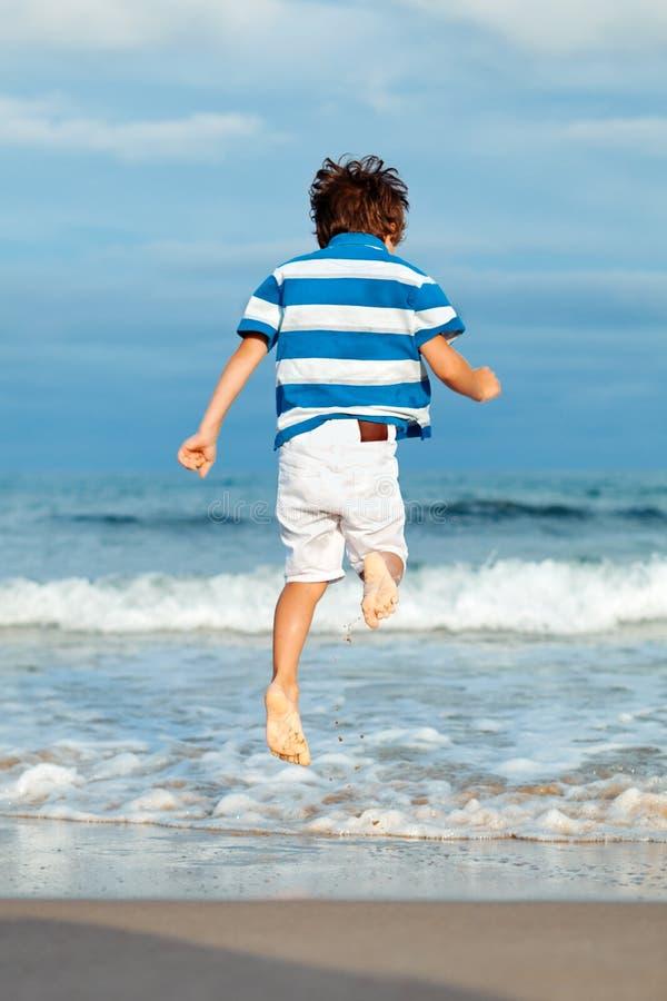 Chłopiec skacze nad fala zdjęcia stock