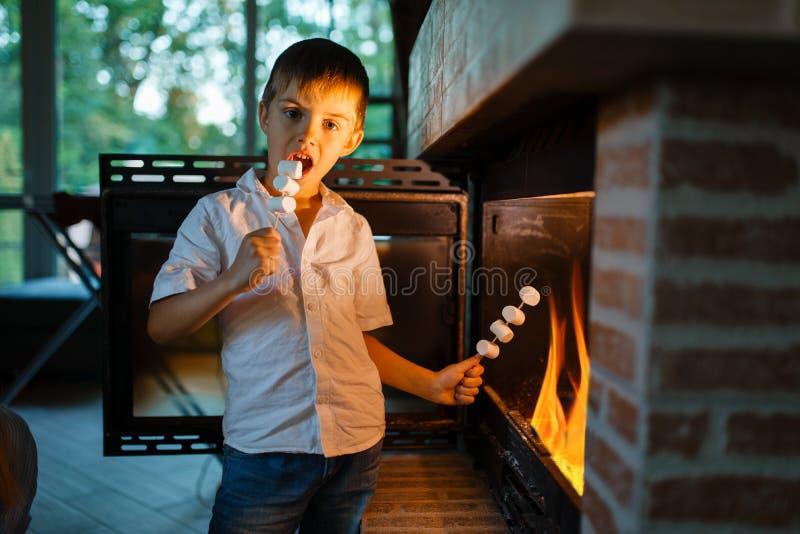 Chłopiec smaży kiełbasy na kiju przy grabą obraz royalty free