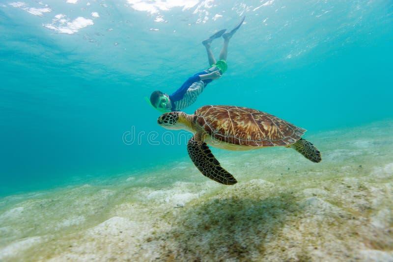 Chłopiec snorkeling z dennym żółwiem fotografia royalty free