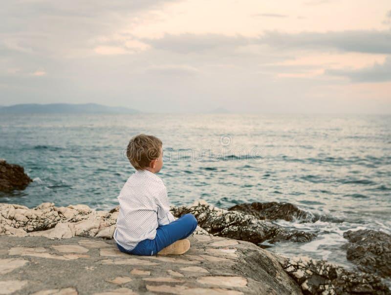 Chłopiec spojrzenia na zmierzchu morza krajobrazie obrazy stock