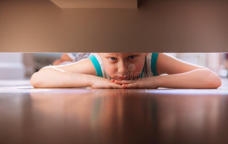 Chłopiec spojrzenia pod łóżkiem obrazy stock