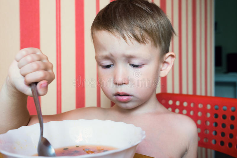 Chłopiec spojrzenia przy pucharem polewka obraz stock