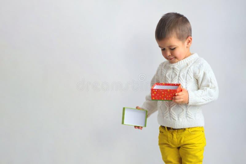 Chłopiec spojrzenia w czerwonym prezenta pudełku fotografia stock