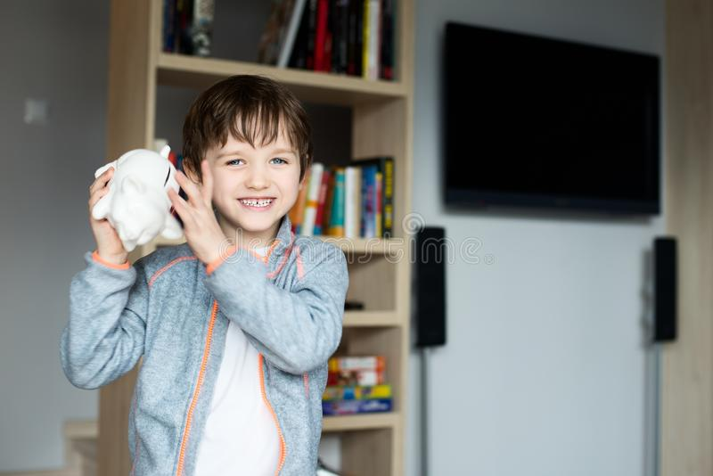 Chłopiec sprawdza zawartość w jego prosiątko bank obraz royalty free