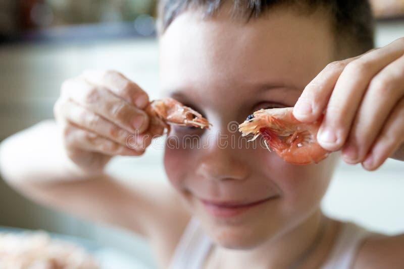 Chłopiec stawia dwa garneli jego oczy jak szkła i uśmiechy obraz stock