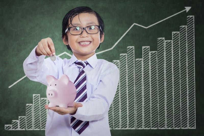 Chłopiec stawia monetę w prosiątko banka zdjęcia stock
