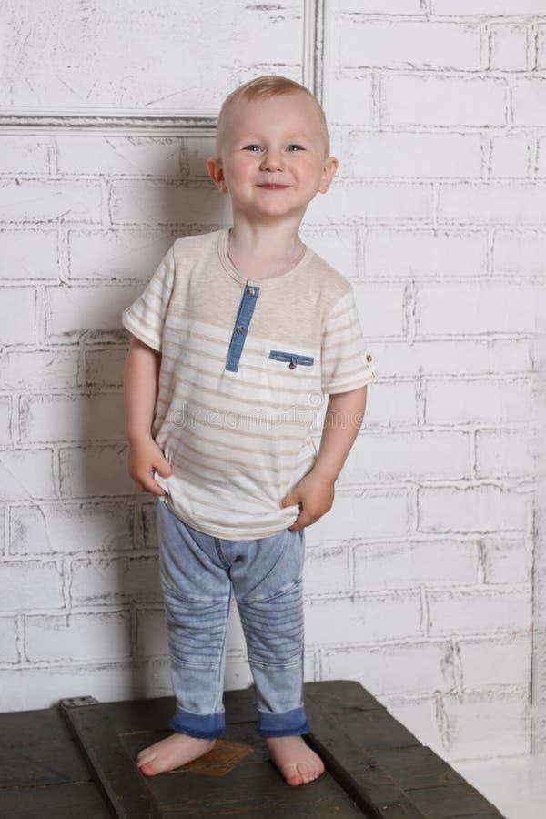 Chłopiec stojaki na drewnianym pudełku i uśmiechy obrazy royalty free