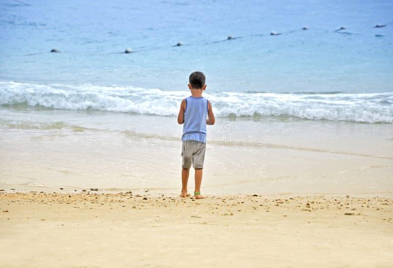 Chłopiec stojaki na plaży zdjęcia royalty free