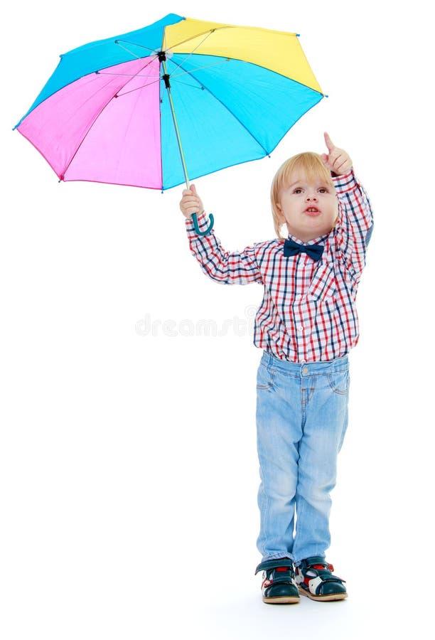 Chłopiec stojaki pod kolorowym parasolem zdjęcie royalty free