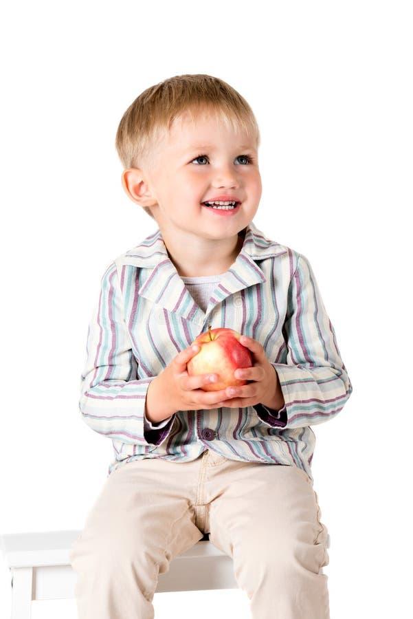 Chłopiec strzelał w studiu na białym tle z jabłkiem zdjęcia stock