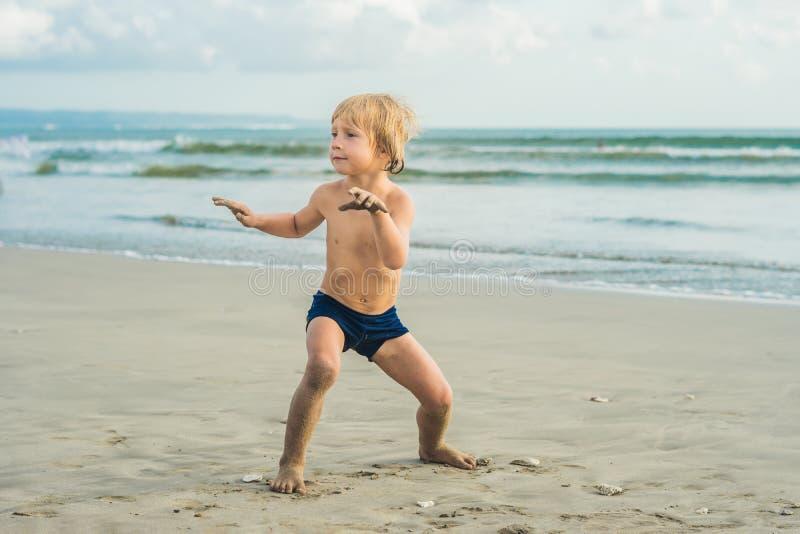 Chłopiec surfing na tropikalnej plaży Dziecko na kipieli desce na ocean fala Aktywni wodni sporty dla dzieciaków Dzieciaka dopłyn zdjęcia stock